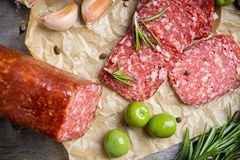 Delicious salami with olives, spices and rosemary Stock Photos