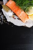 Delicious salmon fillet, rich in omega 3 oil. Aromatic spices and lemon on fresh lettuce leaves on black background. Healthy food, diet and cooking background royalty free stock photo