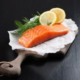 Delicious salmon fillet, rich in omega 3 oil. Aromatic spices and lemon on fresh lettuce leaves on black background. Healthy food, diet and cooking background royalty free stock image