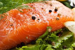 Delicious salmon fillet, rich in omega 3 oil. Aromatic spices and lemon on fresh lettuce leaves on black background. Healthy food, diet and cooking background stock image