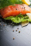 Delicious salmon fillet, rich in omega 3 oil. Aromatic spices and lemon on fresh lettuce leaves on black background. Healthy food, diet and cooking background stock photography