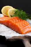 Delicious salmon fillet, rich in omega 3 oil. Aromatic spices and lemon on fresh lettuce leaves on black background. Healthy food, diet and cooking background royalty free stock photos