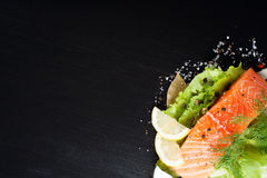 Delicious salmon fillet, rich in omega 3 oil. Aromatic spices and lemon on fresh lettuce leaves on black background. Healthy food, diet and cooking background stock photo