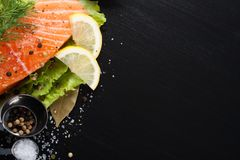 Delicious salmon fillet, rich in omega 3 oil. Aromatic spices and lemon on fresh lettuce leaves on black wooden background. Healthy food, diet and cooking royalty free stock photography