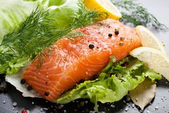 Delicious salmon fillet, rich in omega 3 oil. Aromatic spices and lemon on fresh lettuce leaves on black wooden background. Healthy food, diet and cooking stock image