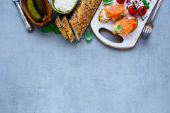 Delicious salmon sandwiches. Tasty smoked salmon sandwiches and fresh ingredients baguette, creamcheese, pickles, basil on grey concrete texture background. Top Royalty Free Stock Photography