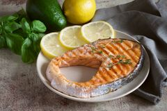 Delicious salmon steak with thin slices of lemon on a beautiful plate. royalty free stock photos