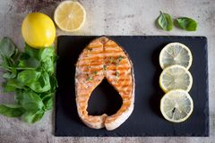 Delicious salmon steak with thin slices of lemon on a plate. royalty free stock image