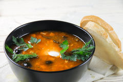Delicious saltwort soup in a bowl and bread. Delicious saltwort soup in a black bowl and bread Stock Photography