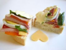 Delicious sandwich. Delicious gourmet sandwich with ham, eggs, mayonnaise, salad, cheese and ketchup. Heart of cheese Stock Photo
