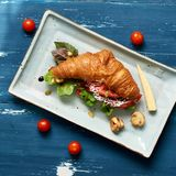 Delicious sandwich made of croissant filled with vegetables. Lettuce, mushrooms and sauce lying on flat rectangular plate standing on blue old wooden surface Stock Photography
