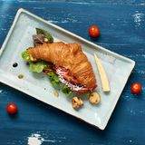 Delicious sandwich made of croissant filled with vegetables. Lettuce, mushrooms and sauce lying on flat rectangular plate standing on blue old wooden surface Royalty Free Stock Photography