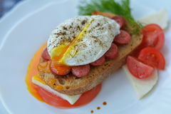 Delicious sandwich with open poached egg, meat, feta cheese, tomato, herbs, pepper - fast breakfast in cafe. Delicious sandwich with open poached egg, meat, feta Royalty Free Stock Photo