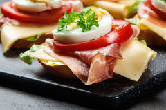 Delicious sandwich with prosciutto ham, cheese, tomato and egg Stock Photo