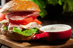 Delicious sandwich with prosciutto ham, cheese and vegetables Stock Photo
