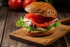 Delicious sandwich with prosciutto ham, cheese and vegetables Stock Photos