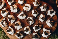 Delicious sandwiches with black caviar and cheese on a wooden Board top view.  stock photos
