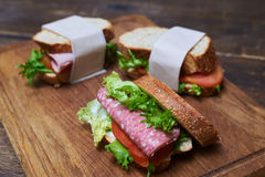 Delicious sandwiches with slices of sausage, tomatoes and lettuc Stock Photos