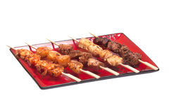 Delicious satay collection on a red plate Royalty Free Stock Image