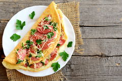 Delicious sausage and cheese omelette on a plate and an old wooden background with blank copy space for text. Eggs omelette Royalty Free Stock Photography