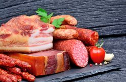 Delicious sausages with garlic and cherry tomato on slate Royalty Free Stock Photo