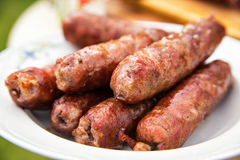 Delicious sausages on plate cooked on barbecue grill. Travel kielbasa cooking. Picnic outdoors Stock Photos