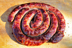 Delicious sausages on wooden plate cooked on barbecue grill. Travel kielbasa cooking. Picnic outdoors Stock Image