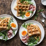 Delicious savory breakfast on a wooden background - boiled eggs, potato waffles and ham. Top view Stock Image