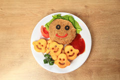 Delicious schnitzel and garnish on a dish in a children's restau Royalty Free Stock Photography