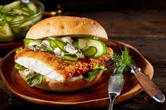 Delicious seafood burger with crumbed fish fillet. Delicious seafood burger with a crumbed fish fillet, cucumber and baby spinach on a plate with utensils over a royalty free stock photos