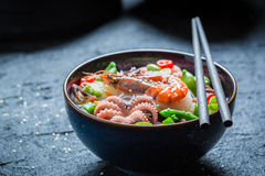 Delicious seafood noodle in dark bowl with chopsticks Royalty Free Stock Images
