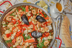Delicious seafood paella at convivial table. Royalty Free Stock Photos