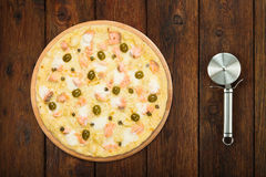 Delicious seafood pizza with olives and steel cutter Royalty Free Stock Photos