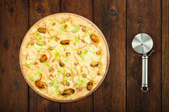 Delicious seafood pizza with olives and steel cutter Royalty Free Stock Images