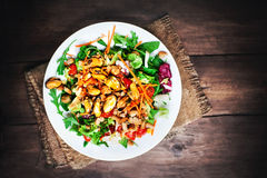 Delicious Seafood salad with vegetables and mussels on wooden ta Stock Photos