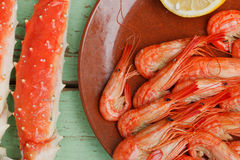 Delicious seafood snack. Of uncracked crab legs and grilled shrimp or prawns on a pottery plate served on an old grungy wooden tabletop Stock Images