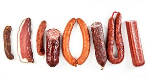 Delicious selection of spicy dried sausages. With a portion of bacon or kassler arranged as a flat lay still life in a row isolated on white in a panorama stock images