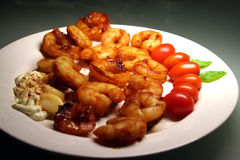 Delicious shrimps plate. Tasty seafood plate with tomatoes and garlic stock image