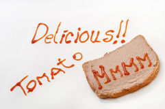 Delicious sign with ketchup and mmmm on the bread with pate Royalty Free Stock Photos