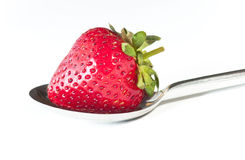 Delicious single strawberry on a spoon, on white. Delicious single fresh English strawberry on a silver spoon on white Stock Photography