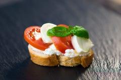 Delicious slice of bread with buffalo mozzarella, tomatoes and fresh basil Stock Photo