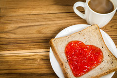 Delicious slice of bread with strawberry jam heart shape Royalty Free Stock Photography