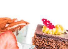Delicious slice of chocolate cake with cream and candy to sugar Stock Photos