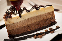 Delicious slice of chocolate cake with syrup and vanilla strokes. On a teble with orchid flower Stock Photography