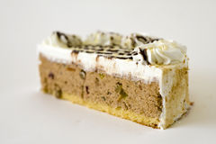 Delicious slice of cream cake. Close up slice of delicious cream cake, isolated on white background Stock Photography