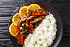 Delicious sliced beef steak with sweet peppers in orange glaze served with rice close-up. horizontal top view. Delicious sliced beef steak with sweet peppers in stock photography