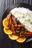 Delicious sliced beef steak with sweet peppers in orange glaze served with rice close-up. Vertical top view. Delicious sliced beef steak with sweet peppers in stock image