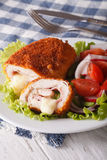Delicious sliced Chicken cordon bleu and a salad close-up. Vertical stock photo