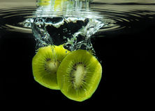 Delicious sliced kiwi dropped in water Royalty Free Stock Photo