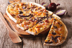 Delicious sliced pie flammkuchen close-up on the table. horizont Stock Images